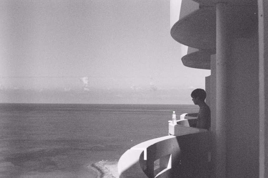 Jeon Jungkook photograohed by Kim Taehyung on a balcony